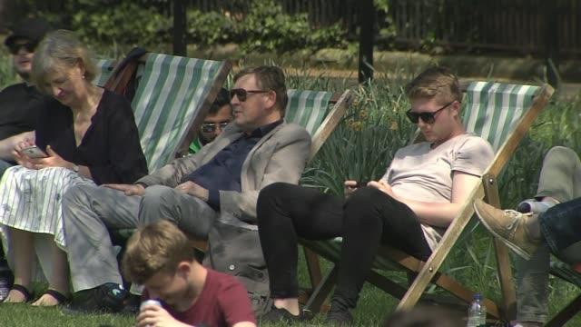 final preparations for london marathon 2018 london ext people sitting on grass in park on sunny day including people sunbathing people sitting on... - deck chair stock videos & royalty-free footage