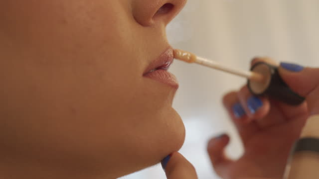 final touch with lip gloss in this make-up look - lip liner stock videos & royalty-free footage