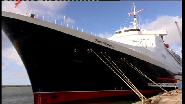 hampshire southhampton ext general views of qe2 at dockside including close up of ship name on side of vessel qe2 as tiger moth aircraft flies... - イングランド サウサンプトン点の映像素材/bロール