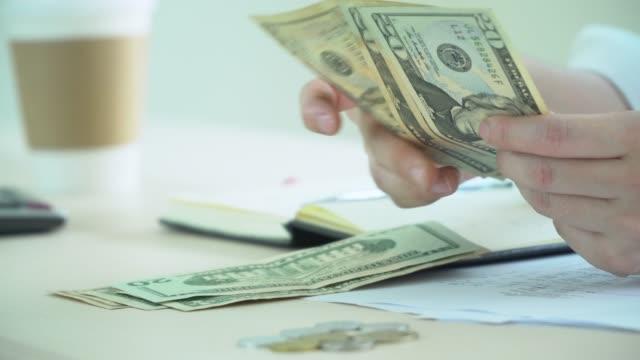 vidéos et rushes de comptabilité financière main - billet de dollars américains