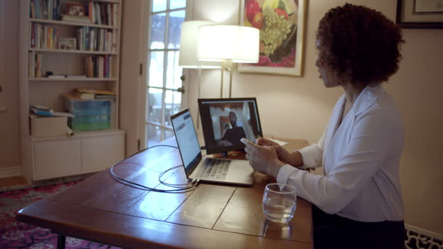 a financial advisor and a client, both working from home offices , meet via video conference to discuss the client's investments - advice stock videos & royalty-free footage