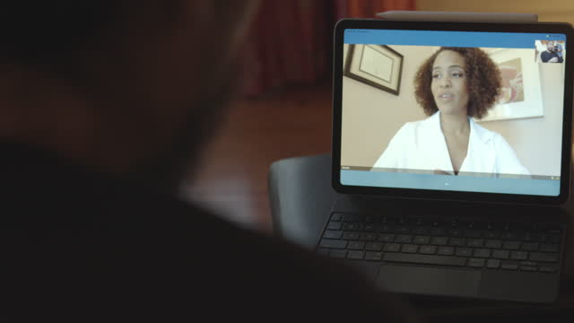 a financial advisor and a client, both working from home offices , meet via video conference to discuss the client's investments - report document stock videos & royalty-free footage