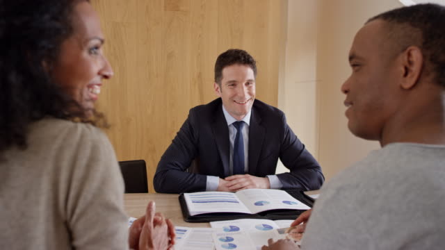 Financial advisor consulting a couple in his office