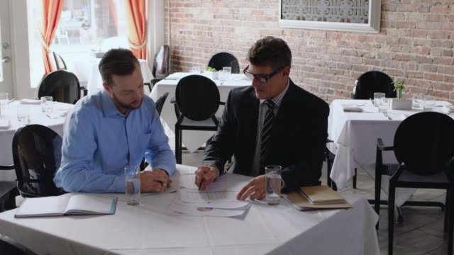 Financial advisor goes over paperwork with restaurant owner