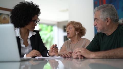 vidéos et rushes de conseiller financier aidant un couple aîné à la maison - montrer la voie