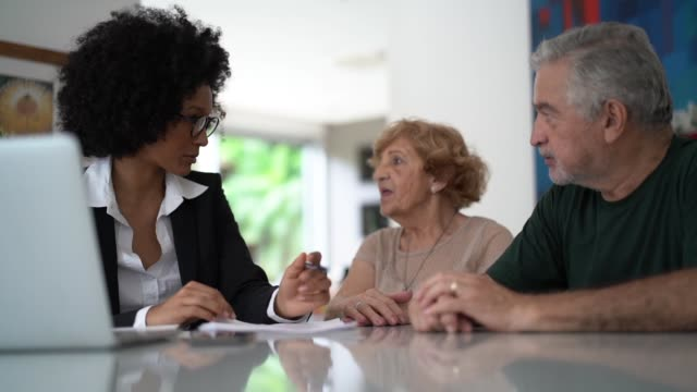 financial advisor helping a senior couple at home - guidance stock videos & royalty-free footage