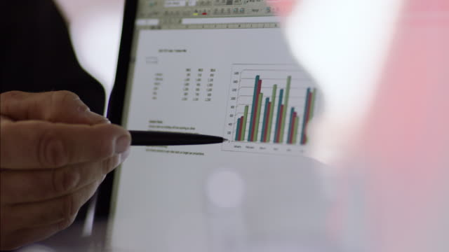 financial advisor points out bar graph results on laptop computer - kommunikation aktivität stock-videos und b-roll-filmmaterial