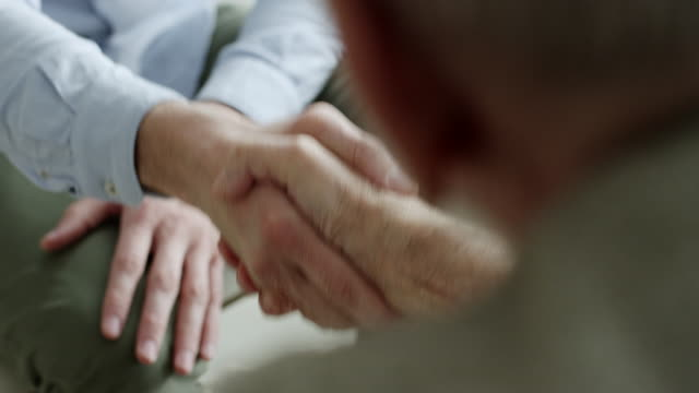 financial advisor shaking hands with older couple - handshake stock videos and b-roll footage