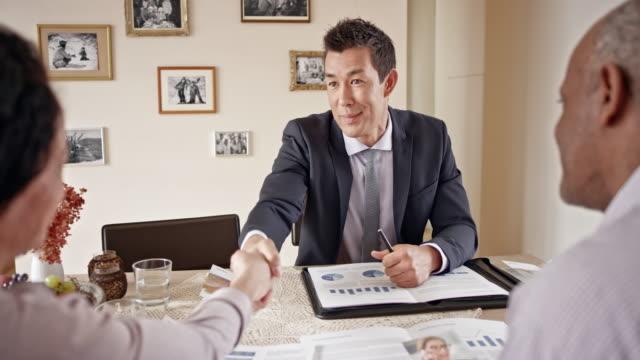 自宅で年配のカップルと握手金融アドバイザー - 助言点の映像素材/bロール