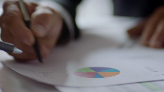 vídeos de stock e filmes b-roll de financial advisor shows important pie chart and bar graph to business owner - pie humano