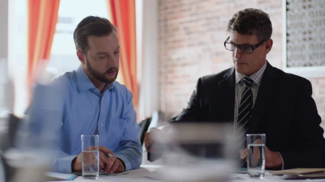 financial advisor shows numbers and figures to restaurant owner in business meeting - papierkram stock-videos und b-roll-filmmaterial