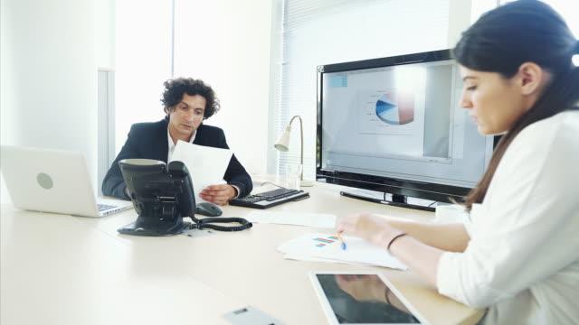 finanzanalyse mit kollegen. - kleines büro stock-videos und b-roll-filmmaterial