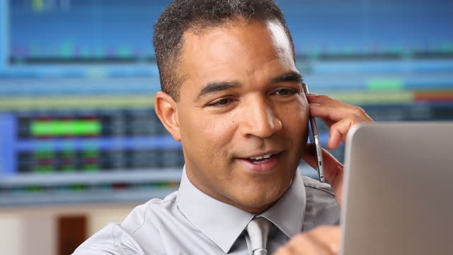 Financial Analyst in Office Talking on the Phone