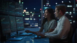 Financial Analyst Talking to Investment Banker in Late Evening at Work. Chatting About Real-Time Stock Chart Data on Tablet Computer. Businesspeople Have a Meeting in Broker Agency City Office.