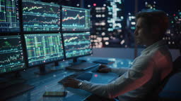 Financial Analyst Working on a Computer with Multi-Monitor Workstation with Real-Time Stocks, Commodities and Foreign Exchange Charts. Businessman Works in Investment Bank City Office Late Evening.