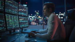 Financial Analyst Working on a Computer with Multi-Monitor Workstation with Real-Time Stocks, Commodities and Exchange Market Charts. Businessman Works in Investment Bank Downtown Office at Night.