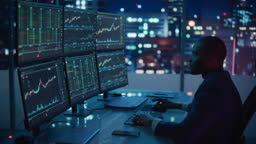 Financial Analyst Working on Computer with Multi-Monitor Workstation with Real-Time Stocks, Commodities and Exchange Market Charts. African American Trader Works in Investment Bank Late at Night.