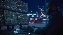 Financial Analyst Working on Computer with Multi-Monitor Workstation with Real-Time Stocks, Commodities and Exchange Market Charts. African American Businessman Works in Investment Bank Late at Night.