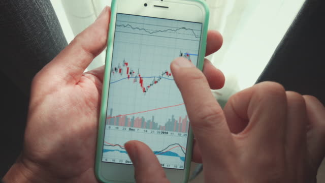 Financiële analisten grafieken op smartphone in de buurt van een venster, Close-up