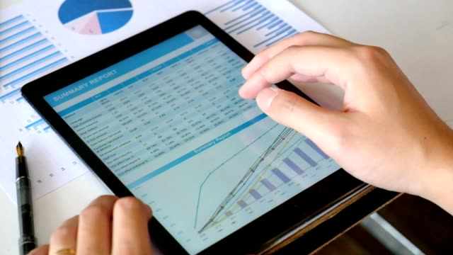 Financial analysts Meeting charts and graphs on the screen of the touchpad