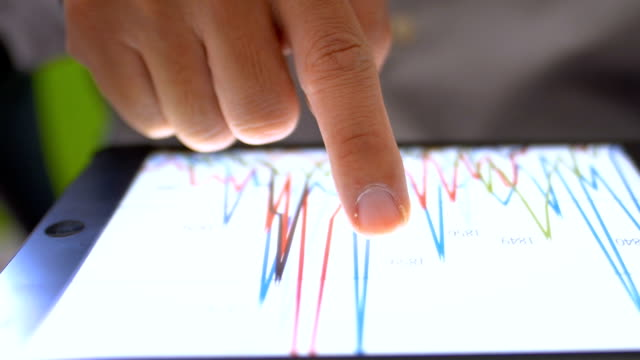 financial analysts see charts and graphs on digital tablet - valuta video stock e b–roll