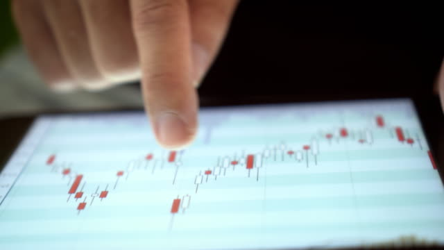 vídeos y material grabado en eventos de stock de analistas financieros ven tablas y gráficos sobre la tableta digital, close-up - global