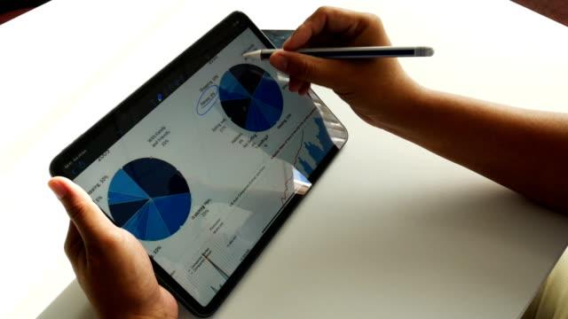 stockvideo's en b-roll-footage met financiële analisten zie grafieken en grafieken op het scherm van de tablet - diavoorstelling