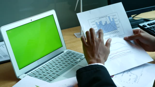 Financial analysts see charts on Doccument with Laptop Green screen, 4k(UHD)