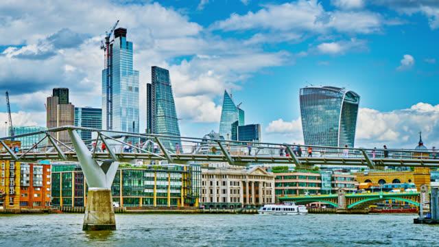 stockvideo's en b-roll-footage met financial district gegroepeerd. mensen lopen door de millennium bridge. - waterkant