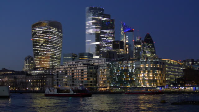 financial district of the city of london at dusk.river thames and tourist boat in the foreground. - international landmark stock videos & royalty-free footage