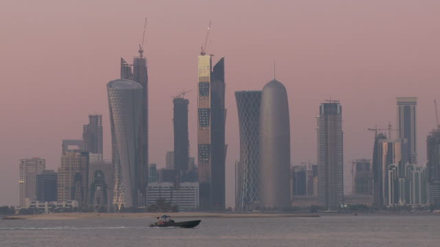 ws financial district skyline seen across doha bay against pink sky at dusk / doha, qatar - doha bildbanksvideor och videomaterial från bakom kulisserna