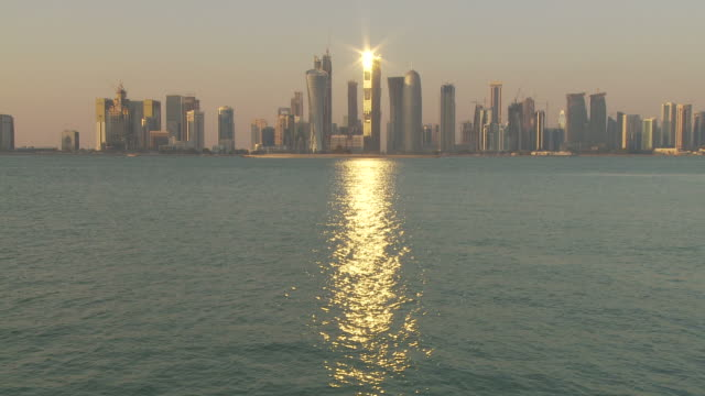 ws financial district skyline seen across doha bay at sunset / doha, qatar - doha stock videos & royalty-free footage