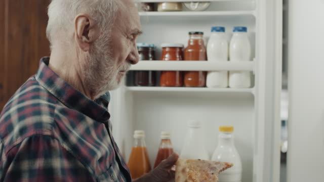 vídeos de stock, filmes e b-roll de encontrar metade de fatia de pizza comida na geladeira - geladeira
