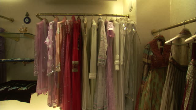 Fine dresses hang on racks in a shop in India.