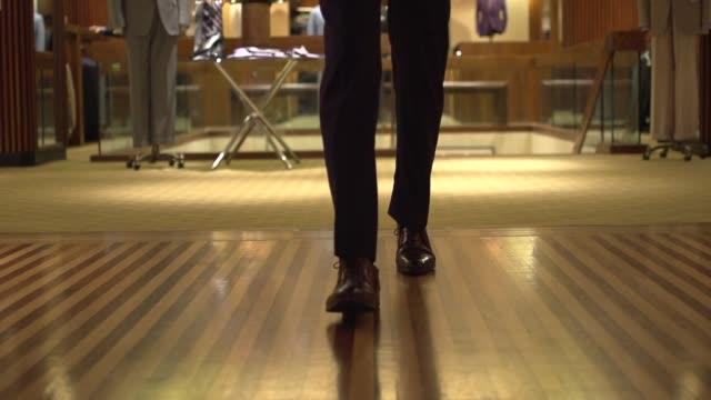 stockvideo's en b-roll-footage met fine herenkleding-wandelen in de hal slow motion - boetiek