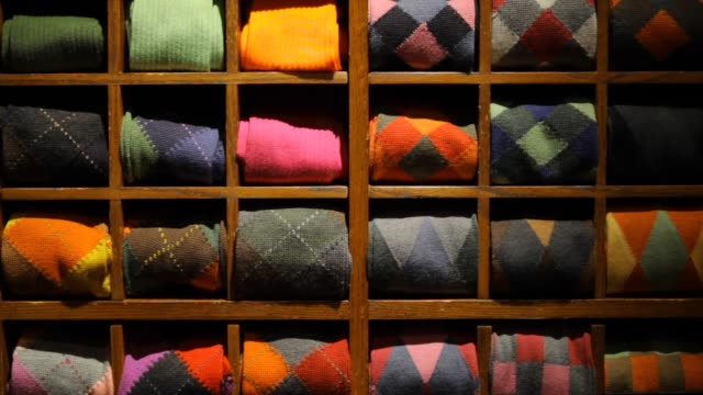fine men's clothing - wall of folded sweaters - scegliere video stock e b–roll