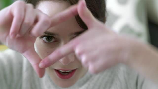 Finger framing portrait close up