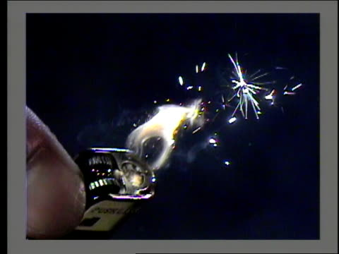 a finger ignites a cigarette lighter. - feuerzeug stock-videos und b-roll-filmmaterial