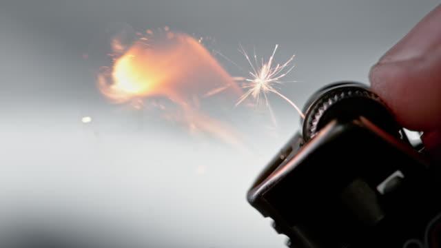 slo mo ld finger zündet das feuerzeug, indem er das funkenrad rollt - feuerzeug stock-videos und b-roll-filmmaterial