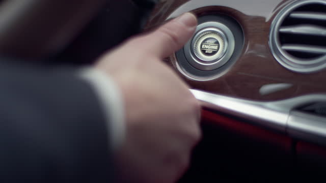 finger pressing 'start engine' button. modern car interior - ignition stock videos & royalty-free footage