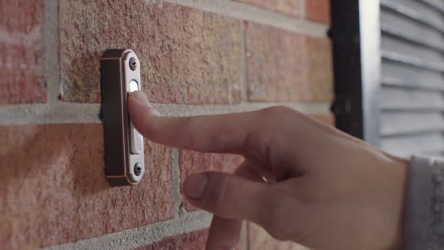 cu. finger pushes doorbell button outside brick house. - nachbar stock-videos und b-roll-filmmaterial