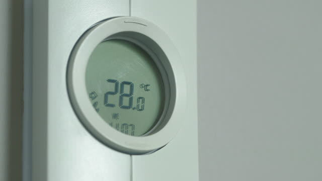 CU of finger raising and lowering the temperature on a thermostat