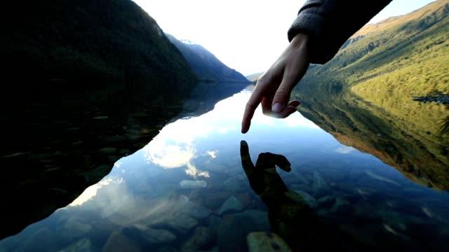 Vinger aanraakt oppervlak van bergmeer, Nieuw-Zeeland