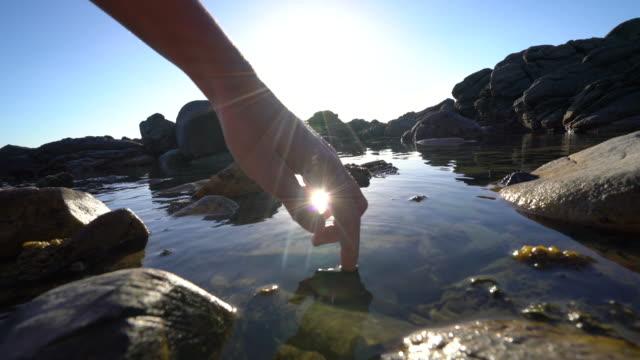 Vinger aanraakt oppervlak van zee vijver