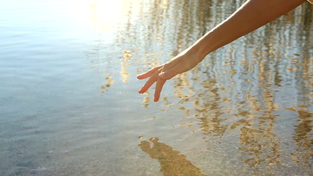 Finger touches surface of tranquil mountain lake