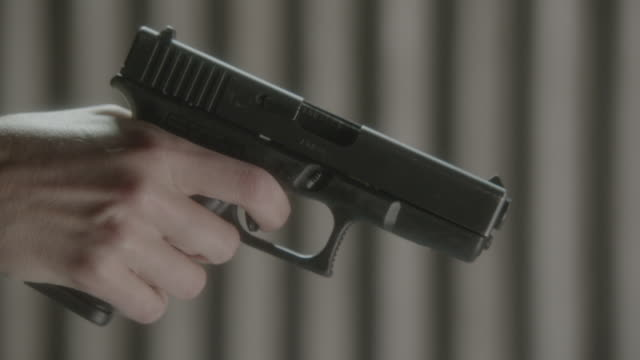 zi finger twitching on handgun trigger - trigger stock videos & royalty-free footage