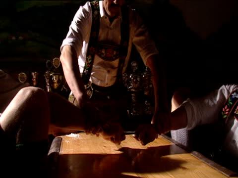 Finger wrestlers in lederhosen position knees against cushioned table for leverage referee begins bout winner pulls loser across table winner celebrates Munich