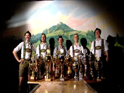 Finger wrestlers in traditional lederhosen display their trophies and jump and cheer in celebration Munich