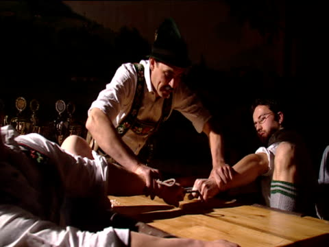 stockvideo's en b-roll-footage met finger wrestlers in tug of war competition across table with knees against cushioned supports for leverage winner pulls loser across table winner's hand raised in victory by referee munich - spelkandidaat