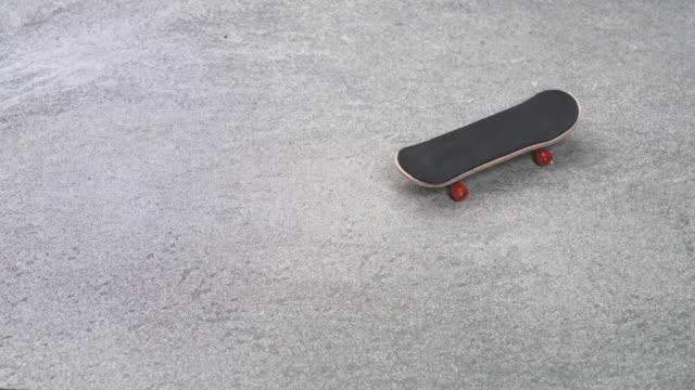 ストーン・グランド・ストップ・モーション・アニメーションでのフィンガーボード・ローリング - 小さな像点の映像素材/bロール